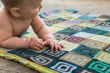 Young Baby Learning To Crawl On Handmade Knitted Blanket; Granny Square Pattern