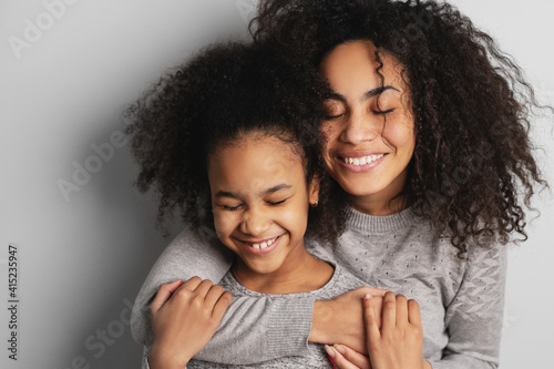 Obraz na plátně Happy african american mom and her little daughter smiling and embracing with eyes closed