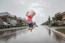 Cute Adorable Girl Running Splashing Under Rain On Street Road. Child Having Fun During Rain Shower Storm. Seasonal Summer Outdoor Activity For Kids. Freedom And Happy Childhood Lifestyle.