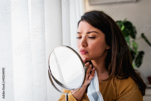 Woman looking herself in the mirror at home standing by the big window. She is concerned about acne, maskne © lordn