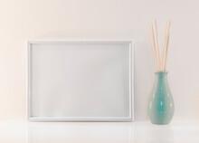 Modèle De Cadre Photo Blanc Avec Espace Vide Pour Logos, Inscription Publicitaire. Cadre En Mode Paysage Sur Un Espace De Travail Avec Un Vase Et Des Bâtons D'encens.
