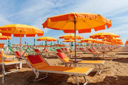 Fotografie, Obraz Bright orange umbrellas and sun loungers on the beach in Rimini, Italy