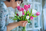 Fototapeta Tulipany - Close up fresh spring pink and white tulips bouquet in a vase and blurred woman enjoying flowers smell with closed eyes in light interior. Slow living. Woman's day. Soft selective focus. Copy space.