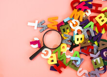 Magnifying Glass With Colorful Alphabet On Pink  Background. Education Concept.