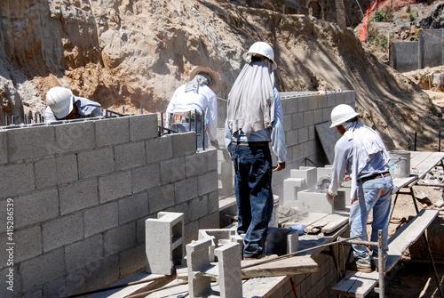 Billede på lærred Masonry crew building a block retaining wall