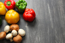 Colorful Vegetables And Peas, Yellow, Green And Red Peppers With Mushrooms On Vintage Gray Wooden Background