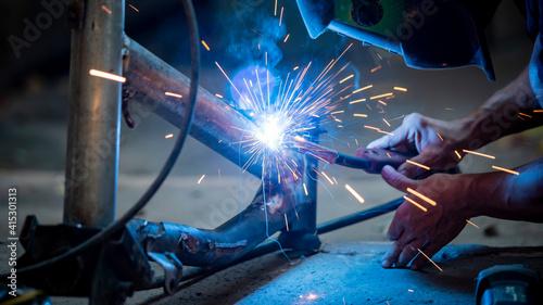 Fotografie, Obraz Welding of steel, sparking, not wearing gloves, light colored like fireworks