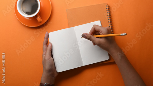 Overhead shot of hands of female holding pen writing on notebook on orange background.