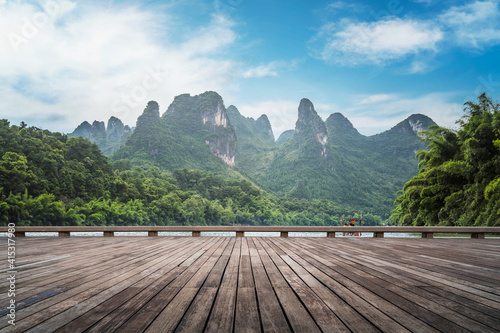 Obraz na plátně Wooden plank road and green mountains and green water natural landscape