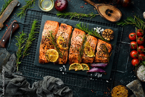 Salmon. Pieces of grilled fish on a black stone background. Recipe. Seafood. Free space for text.