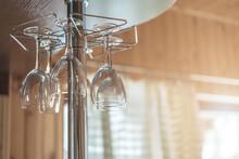 Empty Wine Clean Glasses Hangs Upside Down On Metal Bar Rack In Kitchen