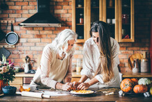 Young Woman And Mother In White Aprons Stand At Large Brown Wooden Kitchen Table And Prepare Tasty Dinner. Senior Mother And Happy Adult Daughter Baking Pumpkin Pie Together At Home.