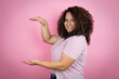 canvas print picture - Young african american woman wearing red stripes t-shirt over pink background gesturing with hands showing big and large size sign, measure symbol. Smiling . Measuring concept.