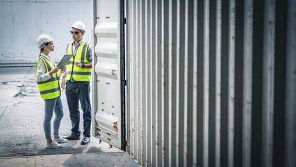 Staff workers in yellow vests and safety helmets inspecting inside of empty shipping container for import and export cargo.