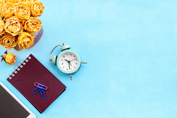 Stationery layout on a blue background. Alarm clock, white postcards, flowers and a smartphone.