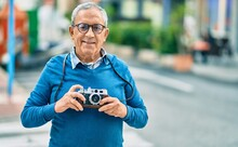 Senior Grey-haired Tourist Man Smiling Happy Using Vintage Camera At The City.