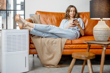 Pretty Woman Sitting Near Air Purifier And Moisturizer Appliance Near Sofa Monitoring Air Quality In Phone. Health Microclimate At Home Concept.