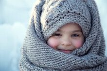 Portrait Of A Little Girl In A Headscarf In Winter.