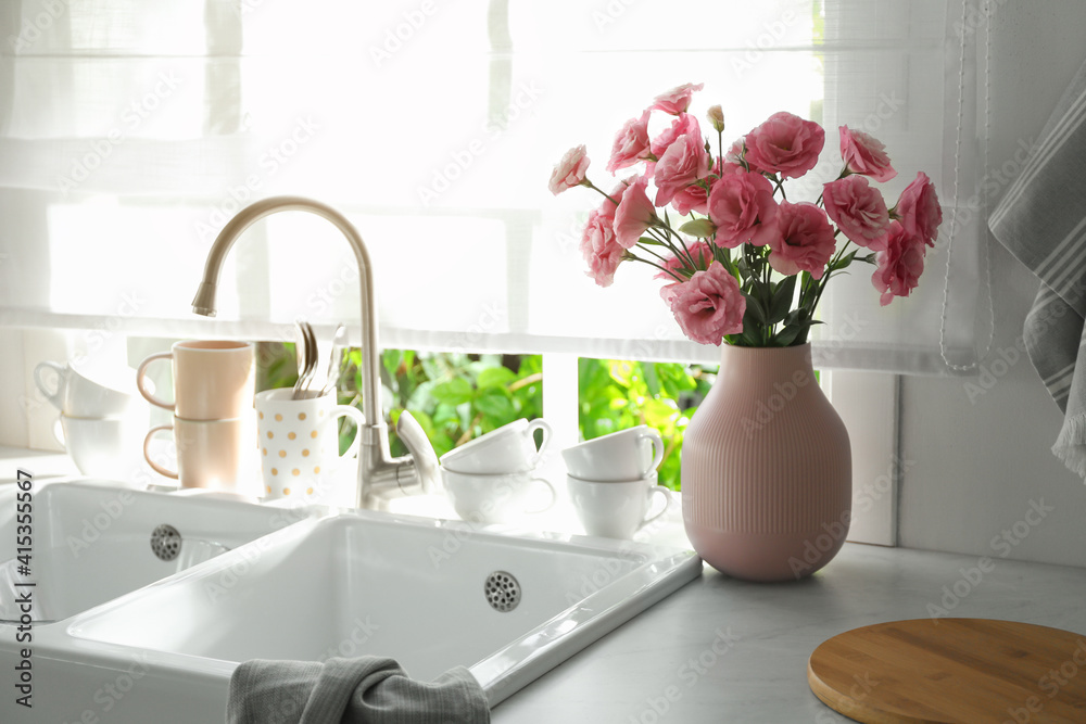 Fototapeta Vase with flowers on countertop near sink against window in kitchen