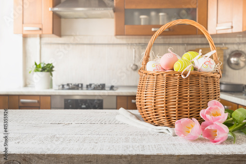 Fototapeta Easter wicker basket with painted eggs and tulips on kitchen white wooden tabletop. Spring composition. Space for text or design. obraz
