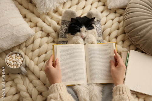 Fototapeta Woman reading book and holding adorable cat on knitted blanket, top view obraz