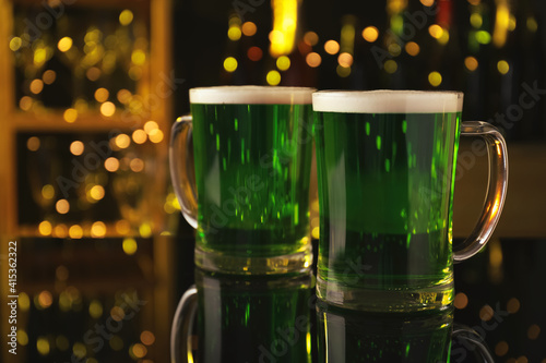 Glasses of green beer on black table against blurred lights. St Patrick's Day celebration © New Africa