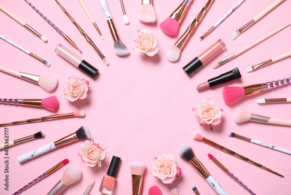 Fototapeta Frame of makeup products and roses on pink background, flat lay. Space for text