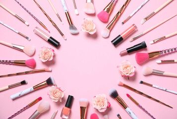 Frame of makeup products and roses on pink background, flat lay. Space for text