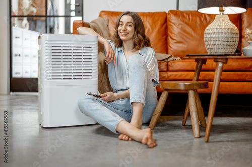 Fototapeta Pretty woman sitting near air purifier and moisturizer appliance near sofa monitoring air quality in phone. Health microclimate at home concept. Looking at camera. obraz