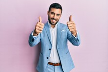 Young Hispanic Businessman Wearing Business Jacket Approving Doing Positive Gesture With Hand, Thumbs Up Smiling And Happy For Success. Winner Gesture.