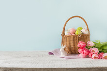 Easter Wicker Basket With Painted Eggs And Pink Tulips On Blue Background With Space For Text.