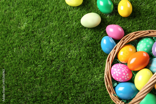 Canvastavla Wicker basket with Easter eggs on green grass, flat lay