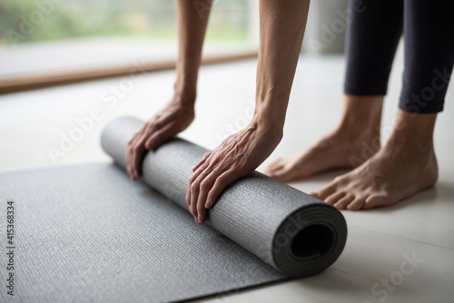 Fotografija Woman rolling up exercise mat and preparing doing yoga or fitness