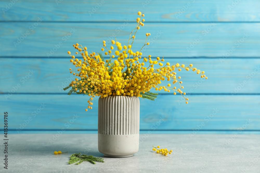 Fototapeta Bouquet of beautiful mimosa flowers on grey table