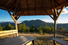 Wooden Gazebo In The Mountains At Sunset With Forest And Mountain Views. Wooden Table And Benches