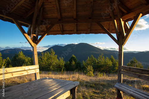 Fototapeta wooden gazebo in the mountains at sunset with forest and mountain views