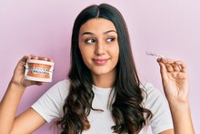 Young Hispanic Woman Holding Invisible Aligner Orthodontic And Braces Smiling Looking To The Side And Staring Away Thinking.