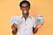 African Handsome Man Holding Dollars Calculating Savings Sticking Tongue Out Happy With Funny Expression.
