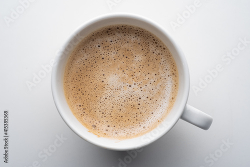 White cup of coffee in soft light isolated on a white background Fotobehang