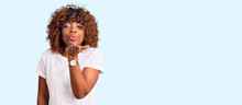 Young African American Woman Wearing Casual White Tshirt Looking At The Camera Blowing A Kiss With Hand On Air Being Lovely And Sexy. Love Expression.