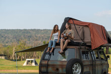 Backpacking Hikers, Sitting On The Roof Of A Van And Playing Guitar, Singing And Having Fun, Resting A Tent On The Roof Of A Car Journey.