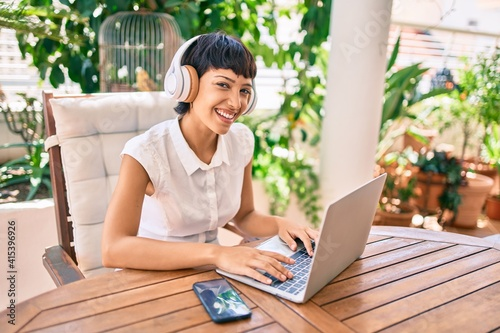 Canvas Print Beautiful woman with short hair sitting at the terrace on a sunny day working fr