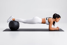 Fitness Woman Doing Plank Exercise On Gray Background. Athletic Girl Working Out With Med Ball