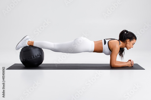 Fototapeta Fitness woman doing plank exercise on gray background. Athletic girl working out with med ball obraz