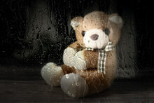 Teddy Bear Behind A Window On A Rainy Day. Children's Toy, Stuffed Animal Behind Wet Glass.