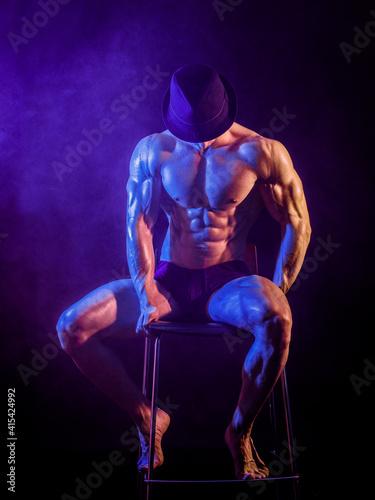 Fotografie, Obraz Shirtless muscular bodybuilder performer sitting on stool wearing hat in studio