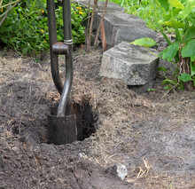 Steel Post Hole Digger With Metal Shovel-like Blades Is Being Used To Create A Deep Hole For A Fence Post With Concrete Bricks And Green Plants In The Background.