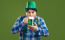 Young Irish Man Celebrating St Patrick's Day And Enjoying Good Alcohol. Portrait Of Funny Curly Guy In Leprechaun Party Hat Drinking Green Beer From Big Glass Mug Standing Isolated On Color Background