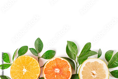 Fotografering Top view of cut orange, grapefruit and lemon on a white table with a copy space