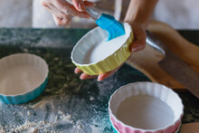 Woman Greasing Baking Mould Before Adding Batter